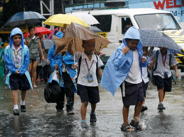 Students walk home in the rain after the suspension of classes due to rainfall from Typhoon Nesat in Quezon City